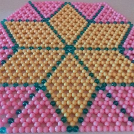 Beaded mat for your table decoration. The strped star design is embedded in light pink beads.
